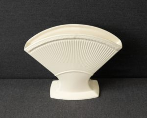 A Wedgwood 'Edme' Napkin Holder.  The item is made of cream colored china in the iconic shape of early Wedgwood wares of the 18th century.  The napkin holder measures 18 cmin height and 24 cm in width.  The item is in a perfect condition.